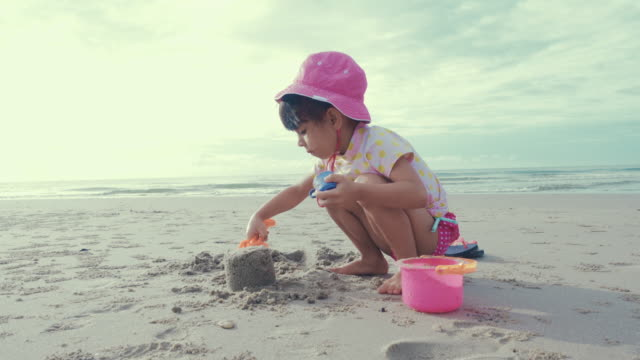 cute girl play sand and happy on the beach - digging stock videos and b-roll footage