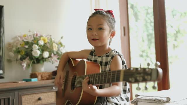ギターストックビデオを再生かわいい女の子 - 再開点の映像素材/bロール