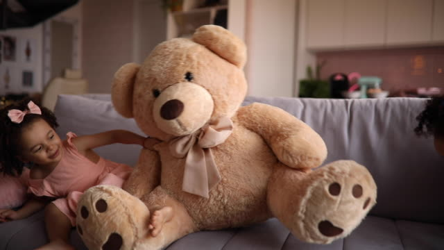 cute girl playing with a big teddy bear - fluffy stock videos & royalty-free footage