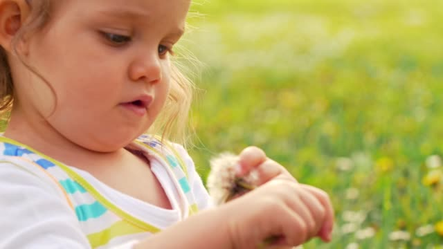 Cute girl playing with dandelion