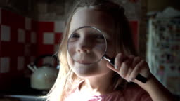 Cute girl playing with loupe