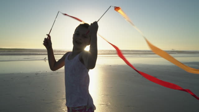 ms cute girl playing with ribbons on the beach at sunset - streamer stock videos & royalty-free footage
