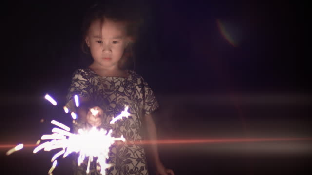 輝きで遊ぶかわいい女の子 - 玩具花火点の映像素材/bロール