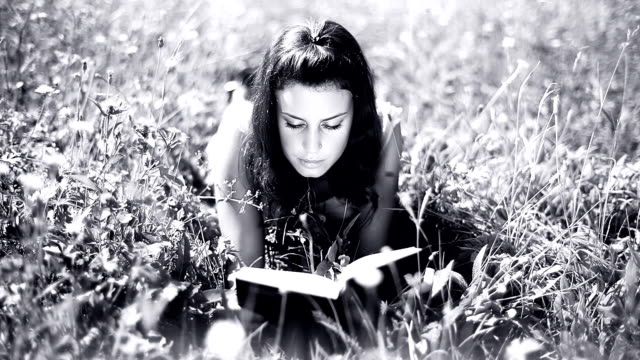 stockvideo's en b-roll-footage met hd: cute girl reading book on a meadow - op de buik liggen
