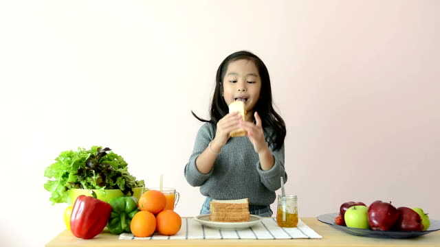 cute girl spreading and eating jam toast at dining table - lunch stock videos & royalty-free footage