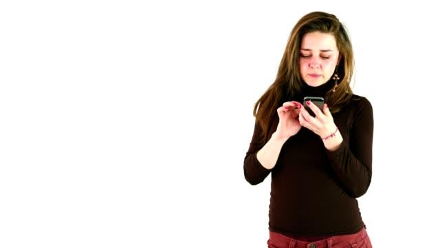 vidéos et rushes de jolie fille à l'aide d'un téléphone intelligent devant un fond blanc - photo messaging