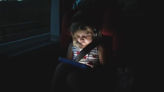 vidéos et rushes de fille mignonne utilisant la tablette numérique dans le train - transports publics
