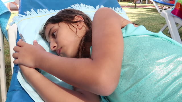 söt tjej med mobiltelefon till stranden - endast flickor bildbanksvideor och videomaterial från bakom kulisserna