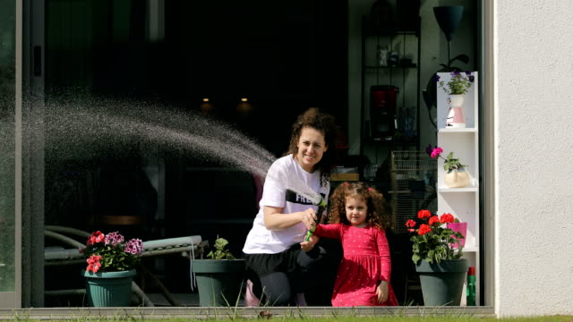 cute girl watering the flowers and grass with her mother - sunny stock videos & royalty-free footage