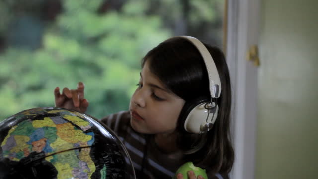 ms cute girl wearing headphones and searching in world map puzzle ball / los angeles, california, united state - world map stock videos & royalty-free footage