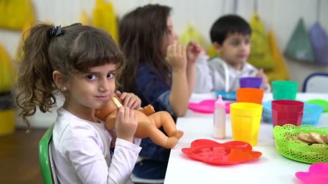 vidéos et rushes de jolie fille avec poupée manger biscuit par des amis - cantine