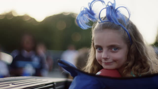 CU SLO MO. Cute girl with silly headband smiles at camera from lawn chair at tailgating event.