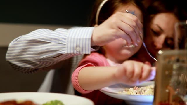 Schattig meisje met geschilderde gezicht eten pasta en het kijken naar cartoons