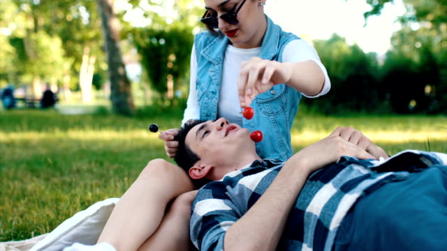 vídeos de stock, filmes e b-roll de namorada bonita alimenta namorado com cereja - flertar