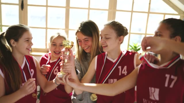 cute girls basketball players celebrating winning a trophy with coach at home - gold medalist stock videos & royalty-free footage