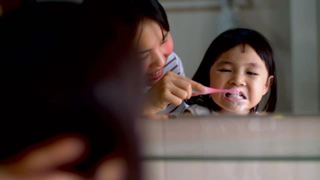 süßes mädchen pinsel ihrer zähne im badezimmer - zahnbürste stock-videos und b-roll-filmmaterial