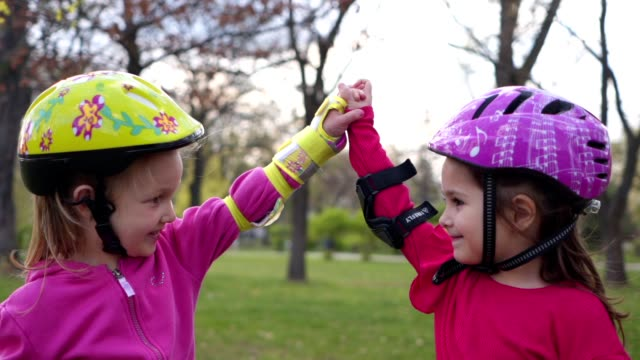 cute girls holding hands upwards after winning a roller skate race - sports helmet stock videos & royalty-free footage