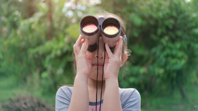 slo mo cute happy children girl using binoculars - curiosity stock videos & royalty-free footage
