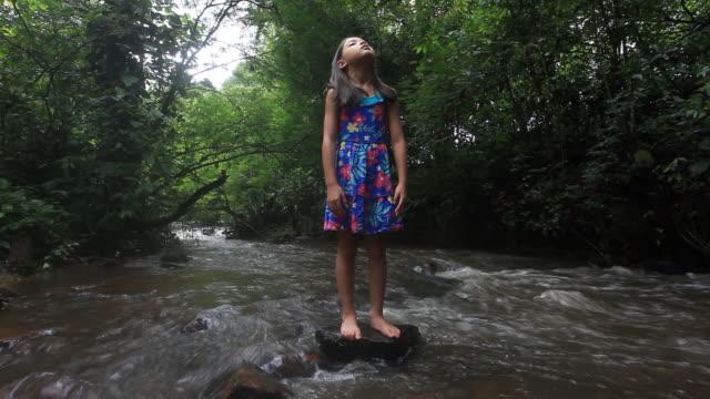 vídeos de stock e filmes b-roll de cute hiker looking above by the stream, standing on stone. - fofo descrição física