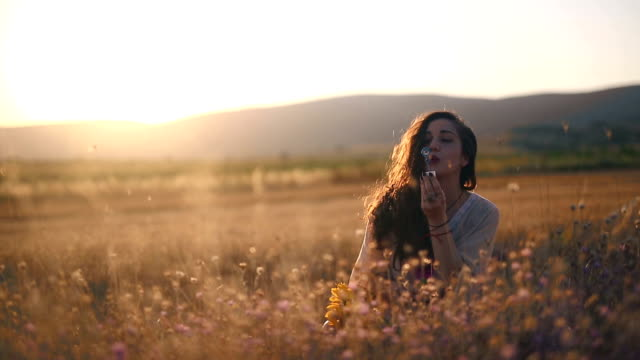 Cute hipster woman in wheat field in sunset