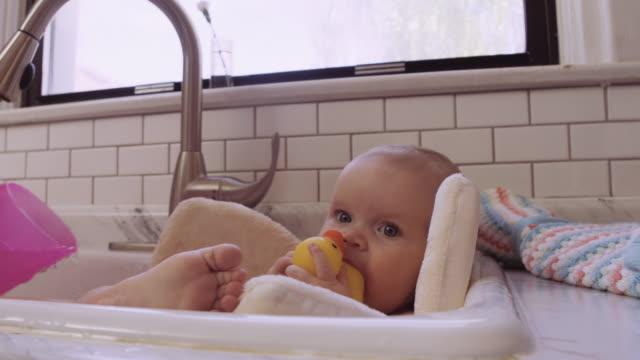 Cute infant taking a sink bath