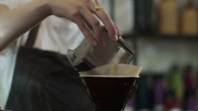 Cute Japanese barista pours grounded coffee beans