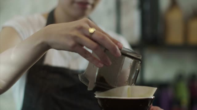 Cute Japanese barista pours grounded coffee beans (slow motion)