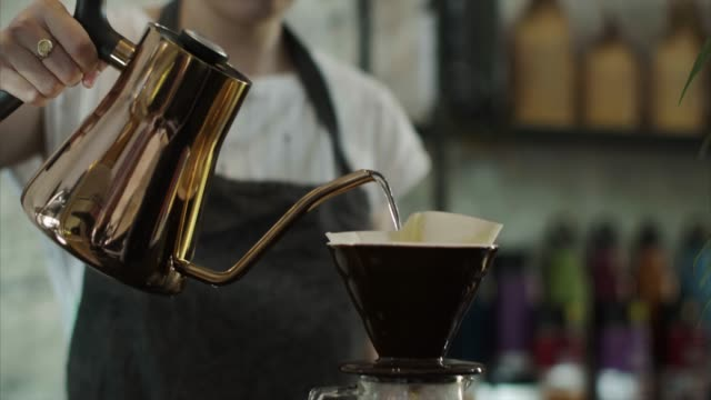 Cute Japanese barista pours hot water over grounded coffee beans