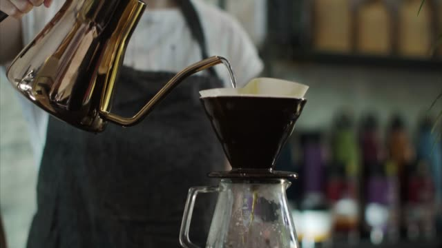 Cute Japanese barista pours hot water over grounded coffee beans (slow motion)