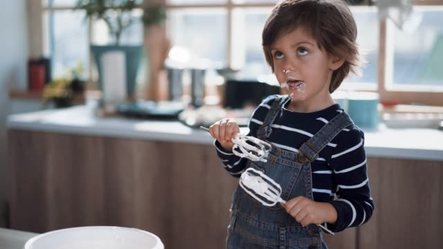 cute kid tasting whipped cream of egg beater - mischief stock videos & royalty-free footage