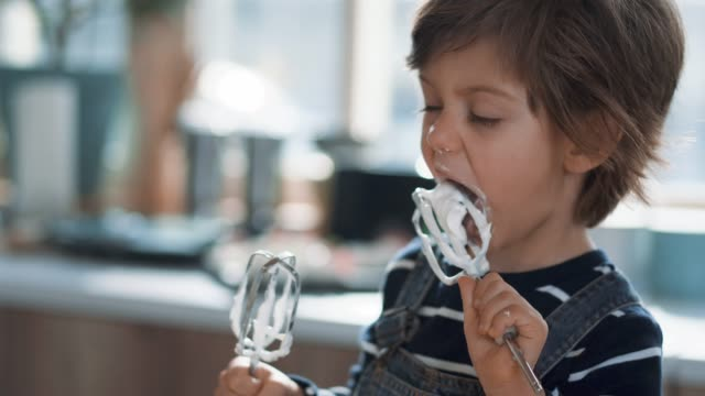 niedliche kid tasting whipped creme of egg beater - milchprodukte stock-videos und b-roll-filmmaterial