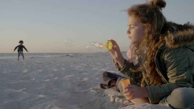cute kids blowing soap bubbles on beach - 6 7 jahre stock-videos und b-roll-filmmaterial