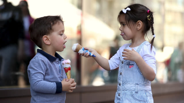 niedliche kids sharing ice cream in front of shopping mall - geschwister stock-videos und b-roll-filmmaterial