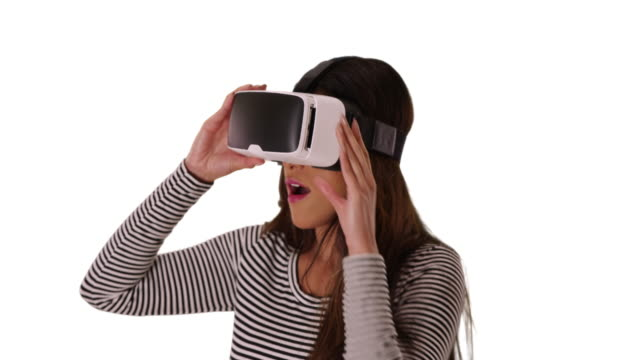 cute latin woman using virtual reality goggles in studio amazed by what she sees - white background stock videos & royalty-free footage