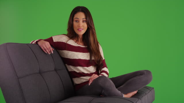 cute latina female lounging on couch, smiling at camera on green screen - long stock videos & royalty-free footage
