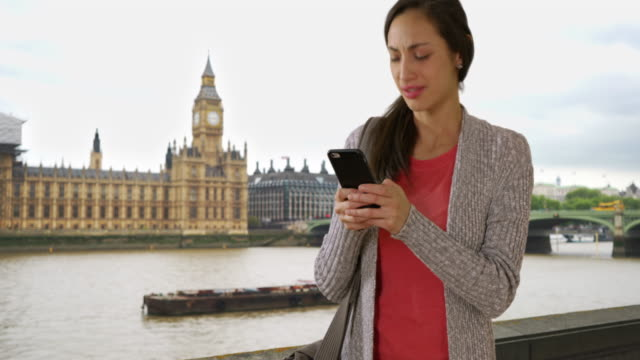 cute latina female texts on cellphone near big ben, waiting for someone - big ben点の映像素材/bロール