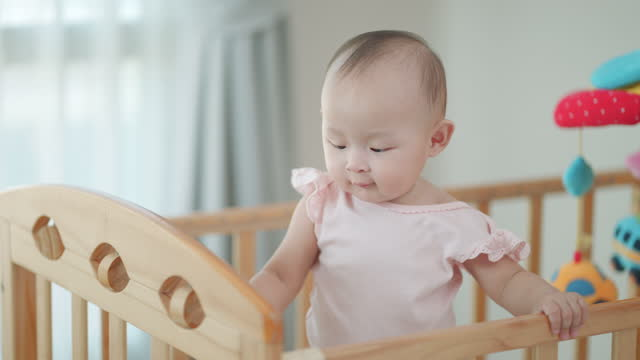 cute laughing asian baby girl standing in a wood round bed for learning to stand in her crib in bedroom at home. - bed furniture stock videos & royalty-free footage