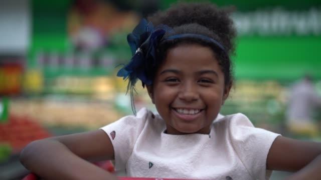 スーパー マーケットでかわいいアフロ ラティーナ女の子 - 中心点の映像素材/bロール