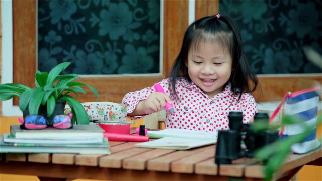cute little asian girl drawing a picture on desk - canocchiale video stock e b–roll