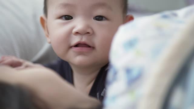 nettes kleines baby junge (6-11 monate) entspannend im bett - 6 11 monate stock-videos und b-roll-filmmaterial