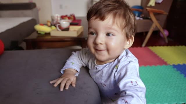 vídeos de stock, filmes e b-roll de bebé pequeno bonito que está para a primeira vez no apartamento com seu animal de estimação ao lado dele - ficando de pé