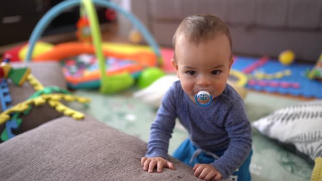 vídeos de stock, filmes e b-roll de bebé pequeno bonito que está em seu playroom perto da cama de sofá - ficando de pé