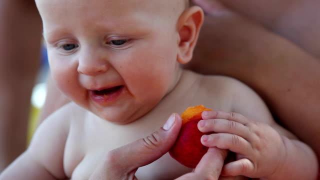 Cute little baby eating sweet juicy peach