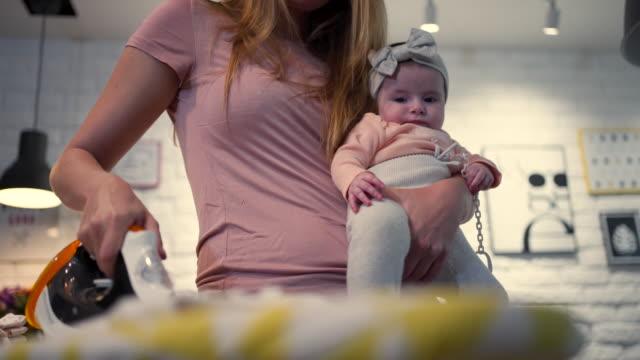 vídeos y material grabado en eventos de stock de lindo bebé sostenido por su madre que está haciendo las tareas domésticas - plancha