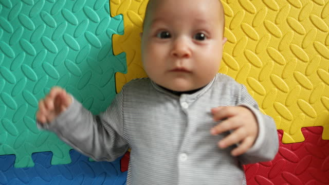 cute little baby playing and looking at the camera. - lying on back stock videos & royalty-free footage