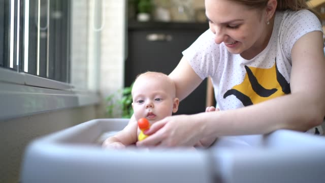 vídeos de stock, filmes e b-roll de bebê pequeno bonito que toma um chuveiro - olhos azuis