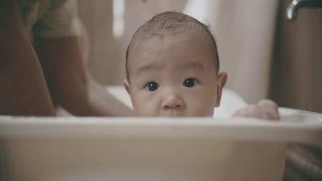 vidéos et rushes de petit bébé mignon prenant une douche avec sa mère - baignoire