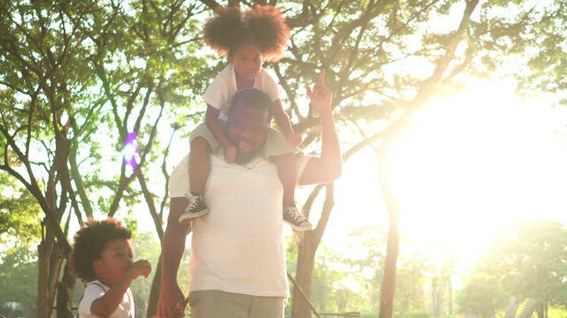 cute little black girl, boy with afro enjoying the day with black father at public park under sunlight. low angle view: dad carrying daughter on shoulder while walking to relax with holding son's hand. concept of family with two children,  simple living. - family with two children stock videos & royalty-free footage
