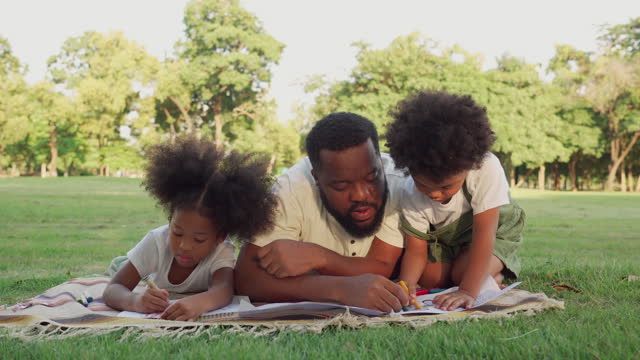 cute little black girl, boy with afro enjoying the day with picnic with black father at public park under sunlight. dad laying down to coloring paper to relax, create a creative idea with daughter, son. concept of family with two children,  simple living. - family with two children stock videos & royalty-free footage