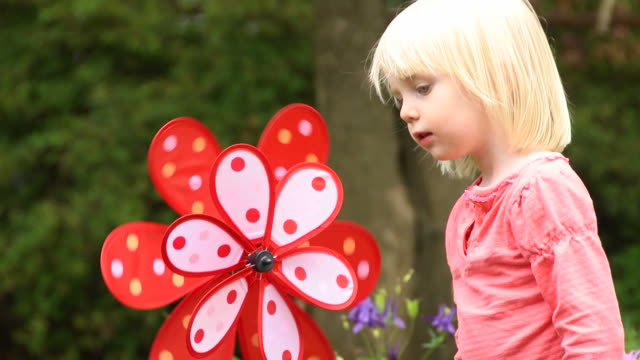 carino piccolo ragazza bionda mette in tappezzi mulino a vento soffia in natura - girandola video stock e b–roll